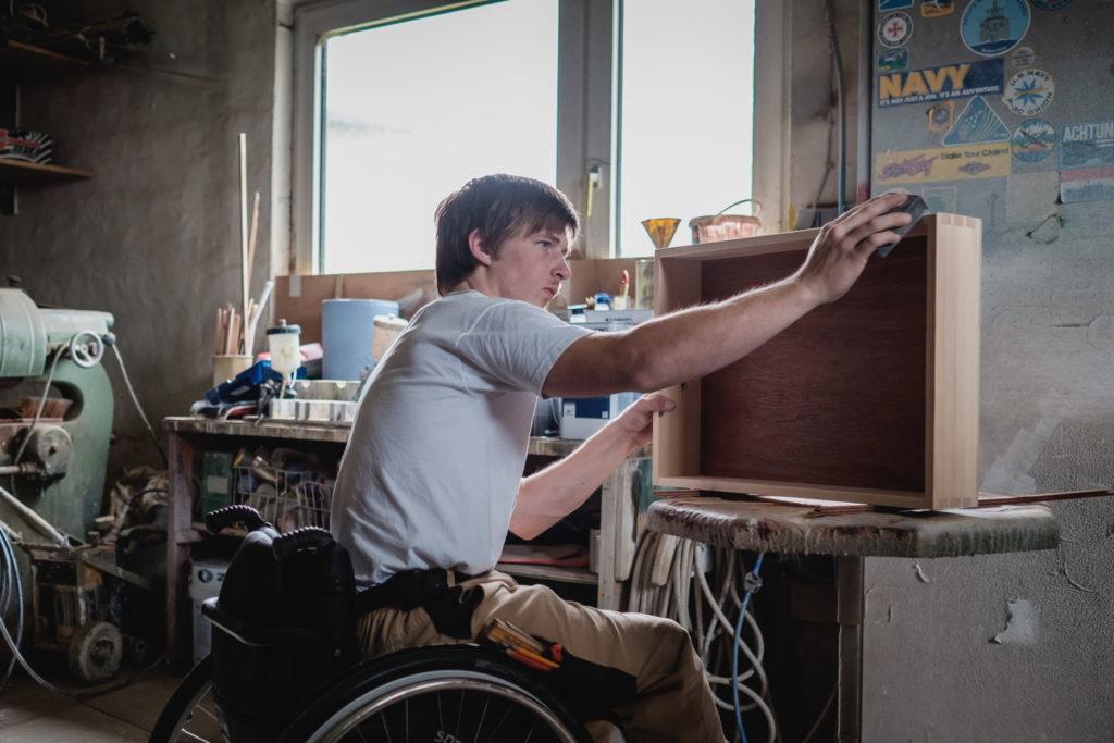 Ein junger Mann im Rollstuhl arbeitet in einer Tischlerwerkstatt an einer Schublade