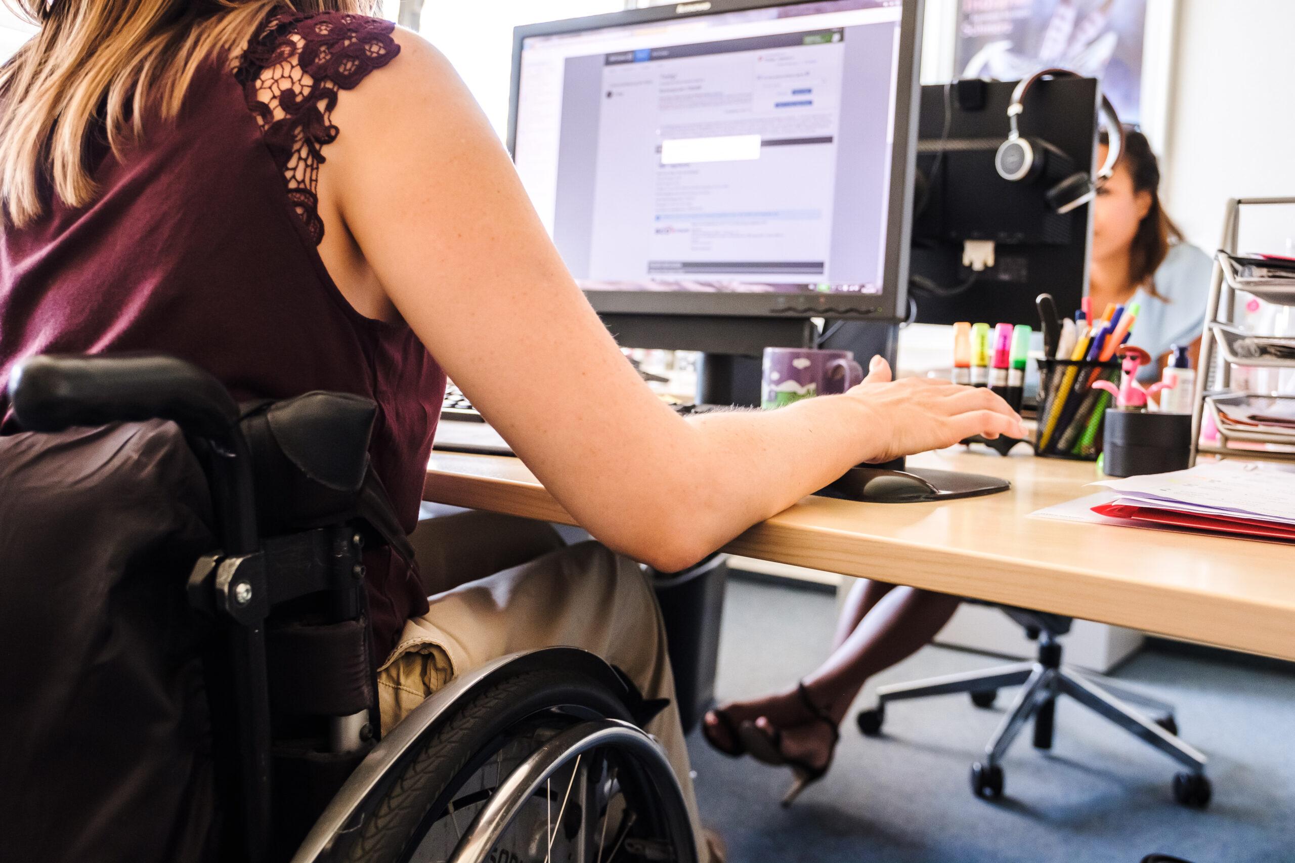 Zwei Frauen sitzen in einem Büro an Computern gegenüber. Eine von ihnen sitzt im Rollstuhl.