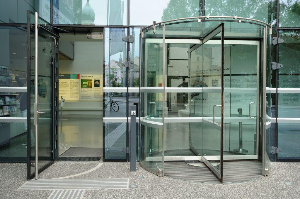 AT: Blick auf den Eingang des Universalmuseums Joanneum in Graz, Österreich. Rechts befindet sich eine Drehtür aus Glas. links ein separater Eingang für Menschen mit Rollstuhl. Ein Knopf zum automatischen Türöffnen ist sichtbar. Auf dem Boden befinden sich taktile Blindenleitsysteme.