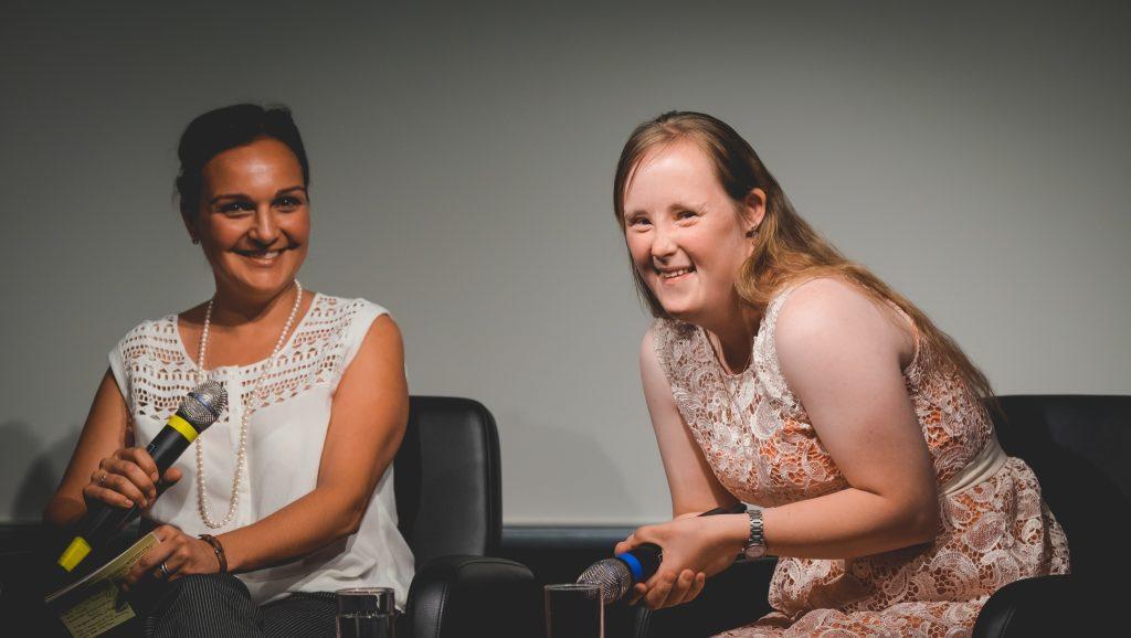 """Ein Podium der Veranstaltung """"Inklusion im Fernsehen"""" der Grimme Akademie bei RTL in Köln. Auf dem Podium sitzen zwei Frauen, eine der beiden hat das Down-Syndrom. Beide halten ein Mikrofon in der Hand und lächeln in die Kamera."""