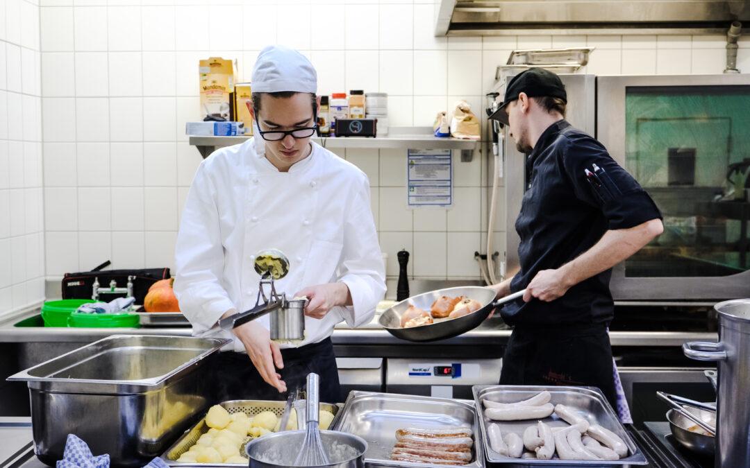 Zwei Personen stehen kochen in einer Großküche.