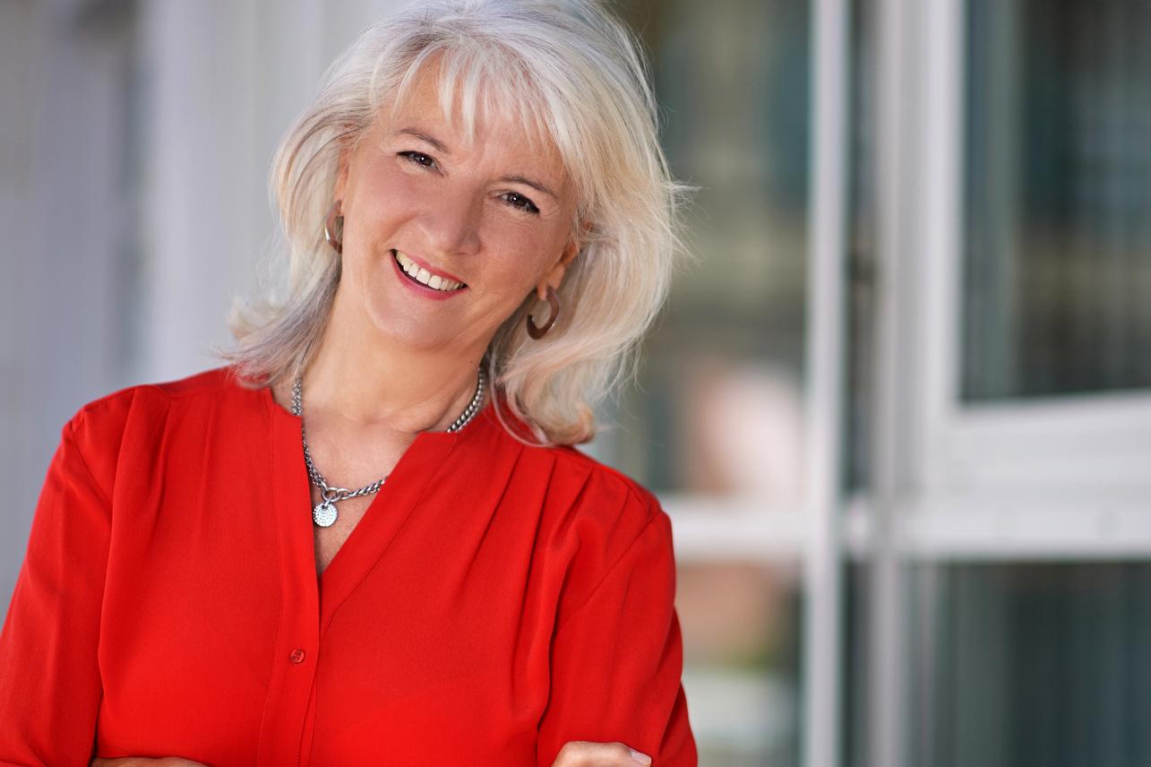 Eine Frau trägt ein rotes Oberteil und lächelt in die Kamera.